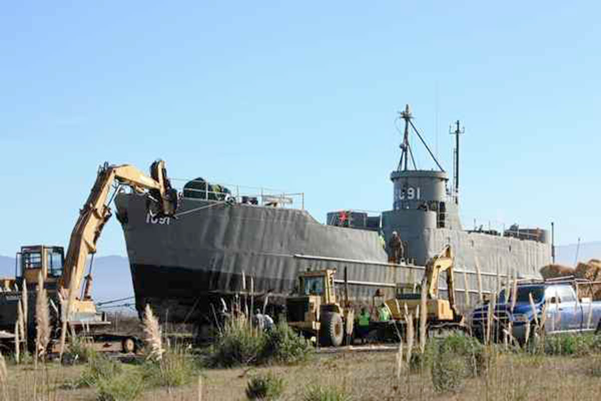 Construction workers pull out the USS LSI(L) 1091 on to Humboldt Bay Harbor  District Recreation and Conservation land in front of the Samoa Cookhouse.