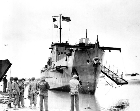 USS LCI(L)-93 aground on Omaha Beach. She still flies her flag, though knocked out of the invasion ripped and wounded on the beach.